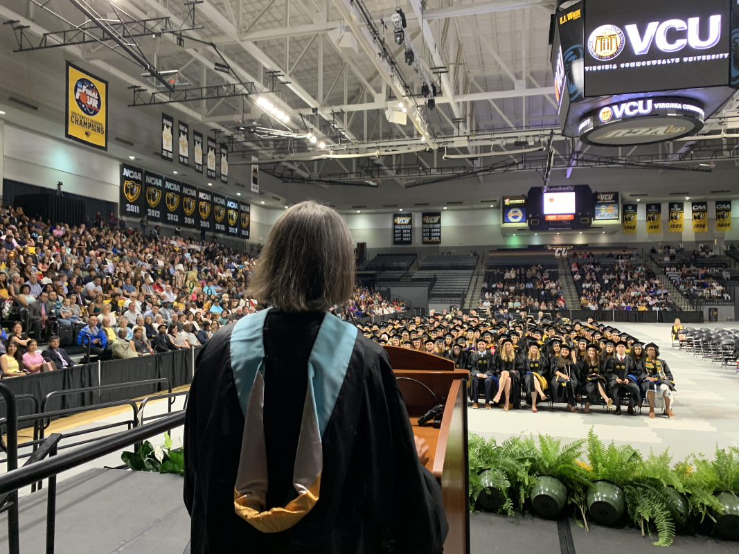 Dr. Sandy Gramling seen from behind facing 2019 graduates